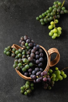 Grape bunches in ceramic cups on a gray background, top view