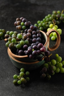 Grape bunches in ceramic cups on gray background