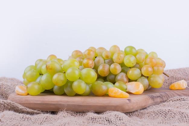 Grappoli d'uva su un piatto di legno con mandarini intorno