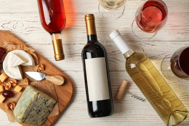 Виноград, сыр, бутылки и бокалы с разным вином на белом деревянном