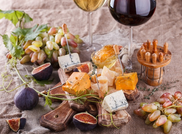 Grape, cheese, figs and honey with a glasses of red and white wine