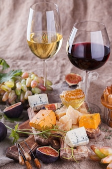 Grape, cheese, figs with a glasses of red  white wine.