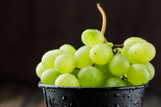Grape cluster in a black bucket on wooden surface, close-up.