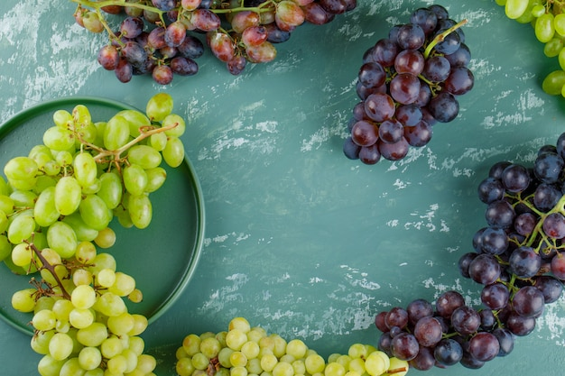 Grape clusters in a tray flat lay on a plaster background