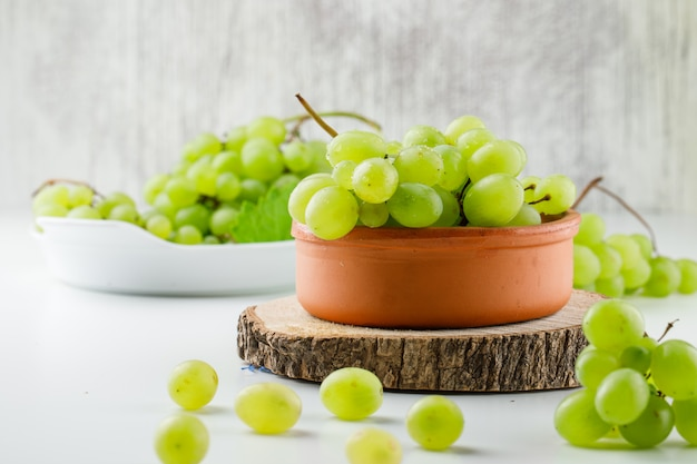 Grape clusters with wooden piece in plates on white surface