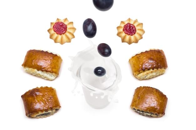 Виноград падает в стакан с молоком с брызгами, вокруг которых вкусное печенье