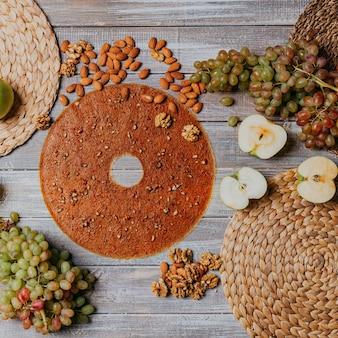 木製のテーブルにナッツとグレープフルーツレザー。ラウンドフルーツレザー。健康食品。リンゴ、バナナ、ブドウの上面図。砂糖なしのグレープフルーツ。