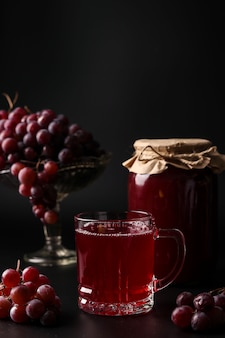 Виноградный сок в стакане и банках, приготовленный в соковыжималке, сбор сока из урожая винограда