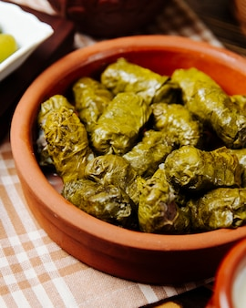 Виноградные листья долма в глиняной тарелке фарш из виноградных листьев специи вид сбоку