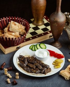 Grape leaves dolma served with yogurt, bread and vegetables