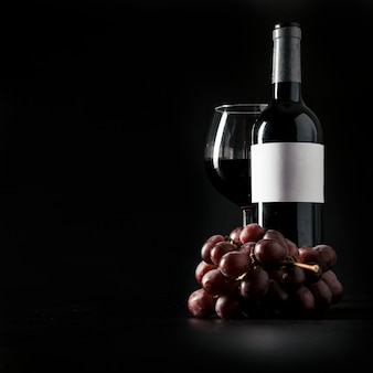 Grape near bottle and glass of wine