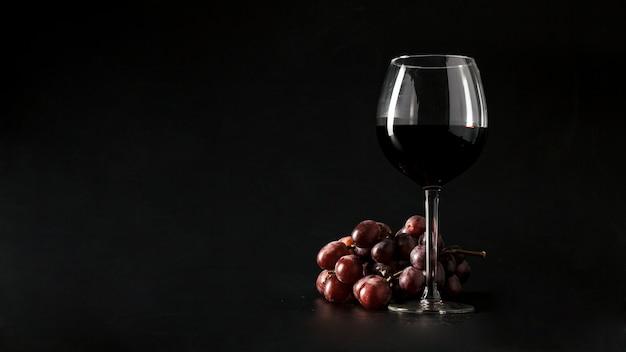 Grape near glass of wine