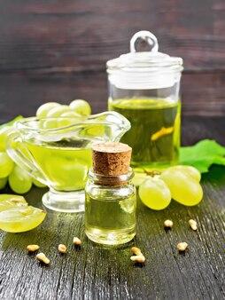 병에 든 포도 기름, 그레이비 보트, 항아리, 어두운 나무 판자 배경에 있는 녹색 포도 열매