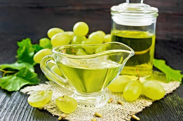 グレイビーボートのグレープオイルと黄麻布の瓶、暗い木の板の背景に緑のブドウの果実