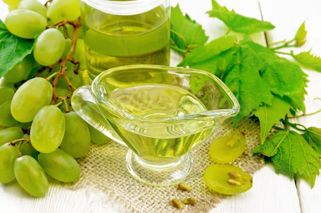 그레이비 보트에 있는 포도 기름과 약탈에 있는 항아리, 밝은 나무 판자 배경에 있는 녹색 포도 열매