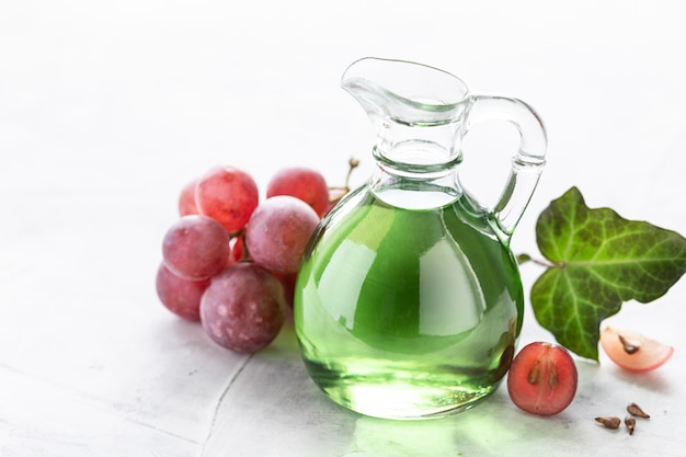 Grape seed oil in a glass bottle with a bunch of grapes