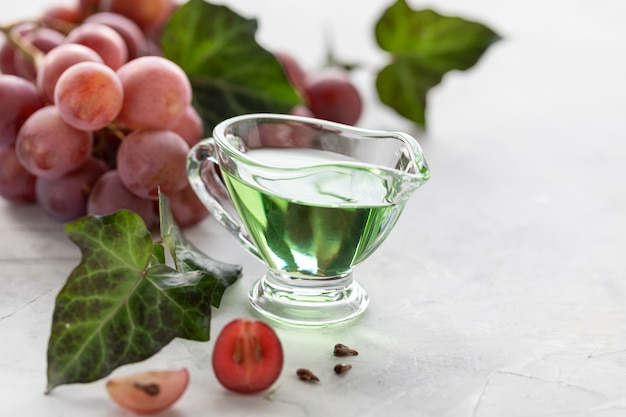 Grape seed oil in a glass bottle with a bunch of grapes.