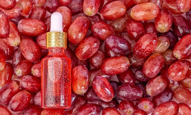병에 들어있는 포도씨 기름은 붉은 신선한 육즙 포도 열매에 놓여 있습니다.