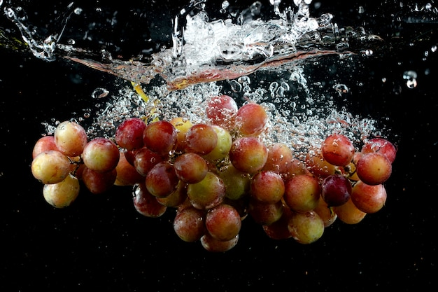 Grape splashing into water in black