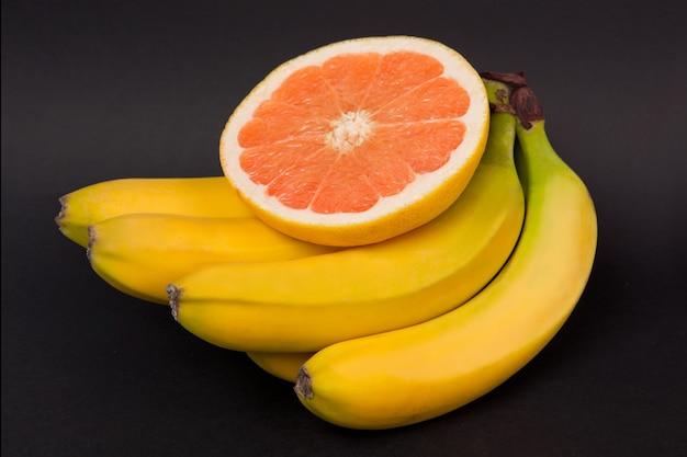 Грейпфрут и банан на черном фоне