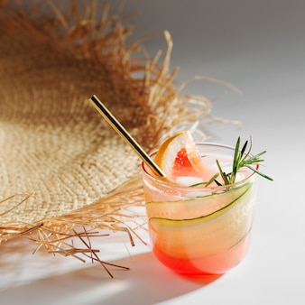 白い背景の上の麦わら帽子とエレガントなメガネのグレープフルーツとキュウリのジンカクテル