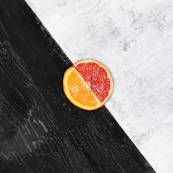 Половинки грейпфрута и апельсина на деревянной тарелке