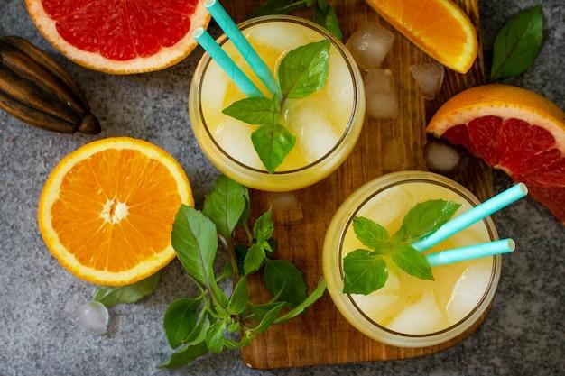 Коктейль из грейпфрута и апельсина с джином или освежающий напиток маргарита со льдом вид сверху плоская планировка