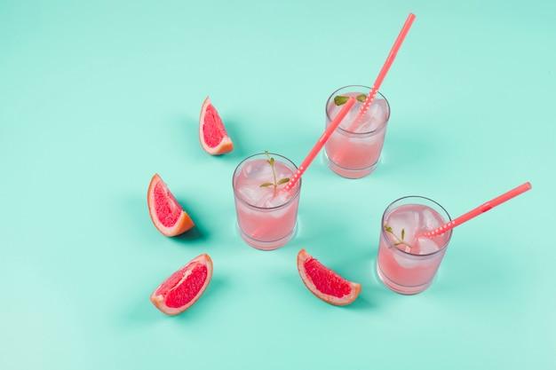 Grapefruit citrus fruit slices and cold juice on mint background