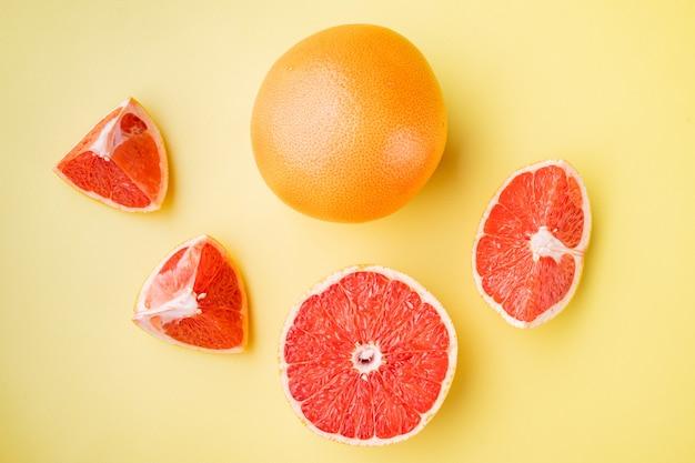 노란색 질감의 여름 배경에 반 세트가 있는 자몽 감귤류 과일, 평면도
