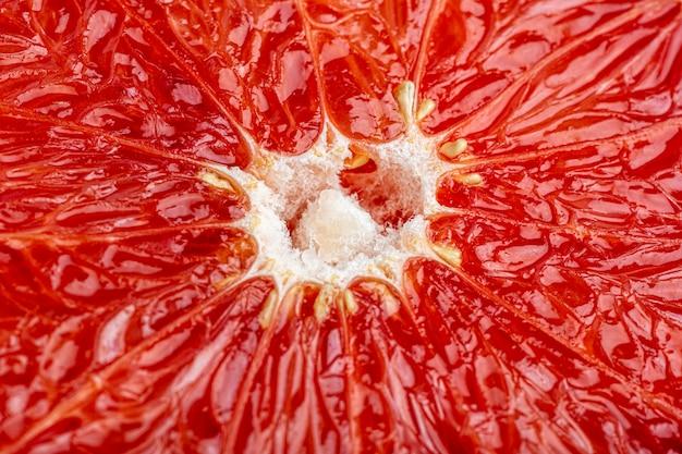 グレープフルーツをクローズアップ。グレープフルーツと柑橘類のジューシーな果肉のテクスチャとパターン。果物のマクロ撮影