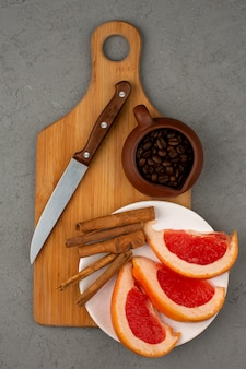 Grapefruit and coffee a top view along with cinnamon on a brown wooden desk and grey