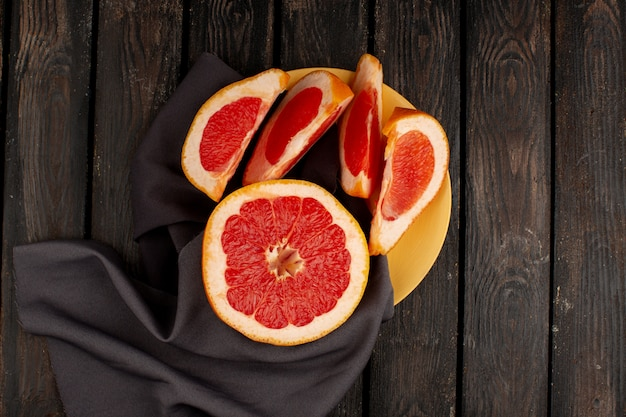 Grapefruit fresh sliced juicy inside yellow plate and on the wooden brown rustic