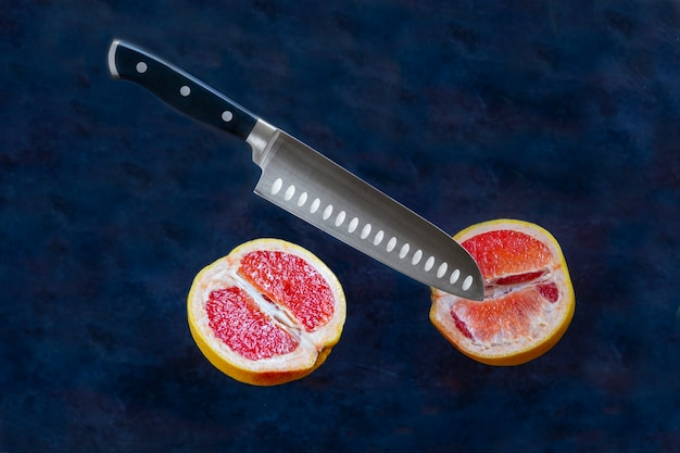 Grapefruit halves cuting with knife on dark background. food levitation