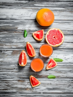 Grapefruit juice in a glass and pieces of fresh grapefruit on wooden table
