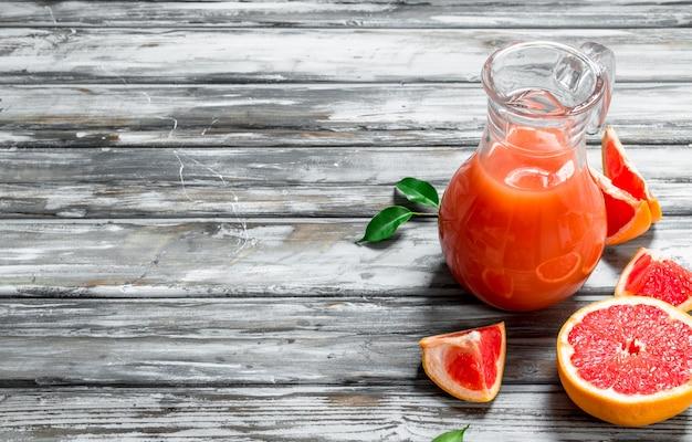 ガラスピッチャーのグレープフルーツジュース。木製の背景に