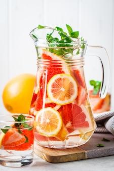 Grapefruit lemonade with lemon and mint in glass jug.