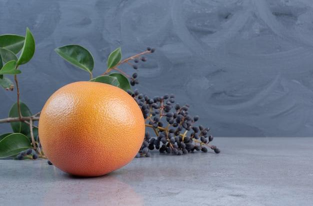 Грейпфрут рядом с декоративной веткой с ягодами и листьями на мраморном фоне.