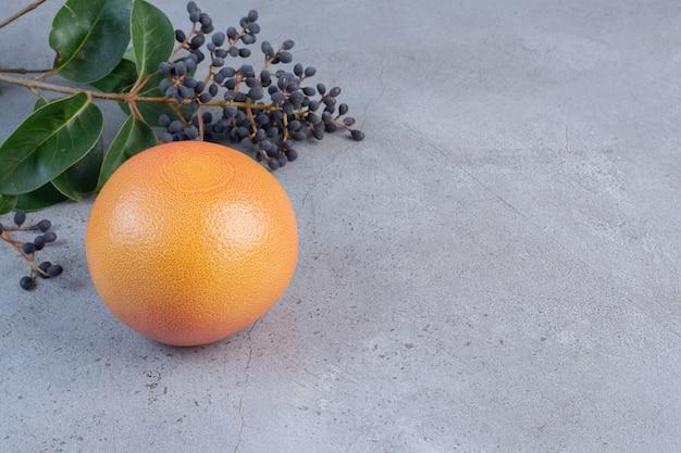 大理石の背景にベリーと葉の装飾的な枝の横にあるグレープフルーツ。