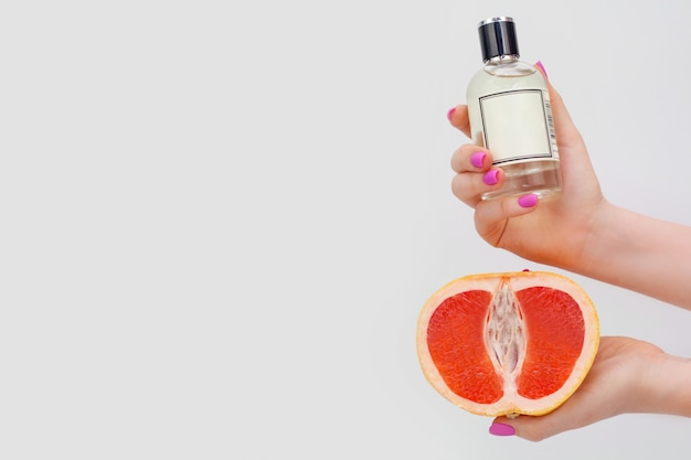 女性の手でボトルにグレープフルーツオイルと彼女の手でジューシーなグレープフルーツ、白い壁にコピースペース。柑橘系の香りやアロマテラピー、ボディケアのコンセプトです。