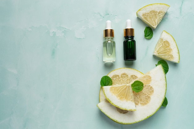Bottiglia di siero olio di pompelmo messa su sfondo verde chiaro