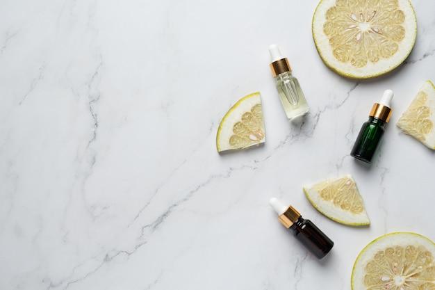 Bottiglia di siero olio di pompelmo messa su sfondo bianco marmo