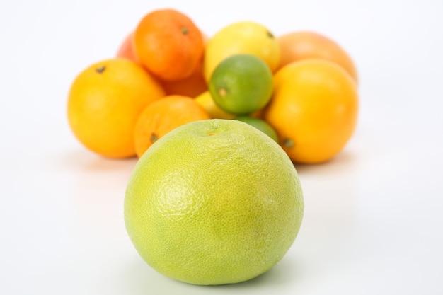 Грейпфрут на фоне различных цитрусовых на белом фоне