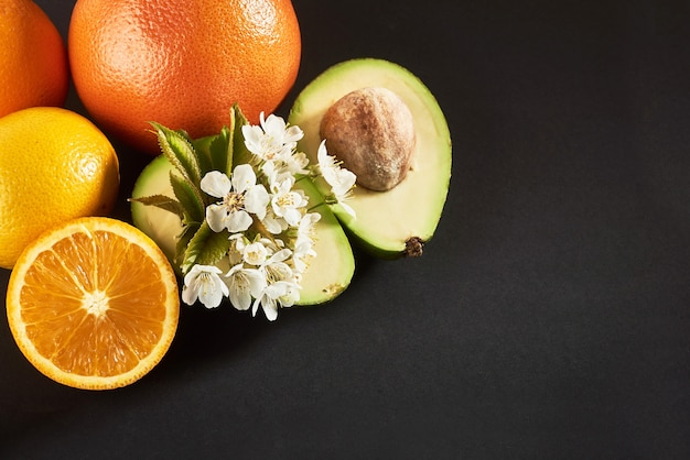 グレープフルーツ、オレンジ、アボカド、黒に分離。
