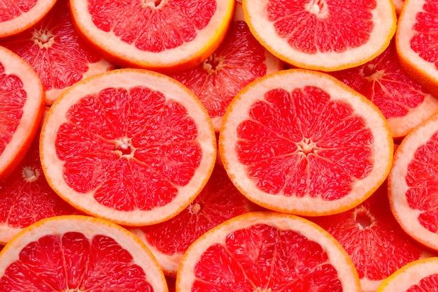 Предпосылка ломтиков грейпфрута красная сочная. вид сверху