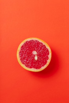 Grapefruit slice isolated on red surface