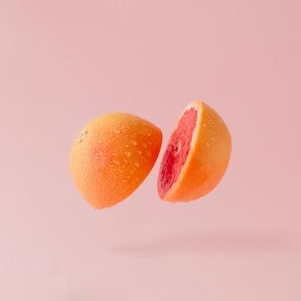 Grapefruit sliced on pastel pink surface