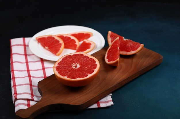 Grapefruit sliced on the wooden board.