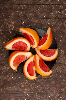 Grapefruit slices fresh juicy mellow inside black plate on a wooden rustic brown desk
