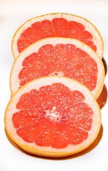 Ломтики грейпфрута, изолированные на белом фоне, вид сверху. красный грейпфрут.