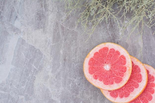 Ломтики грейпфрута на каменном фоне с растением.
